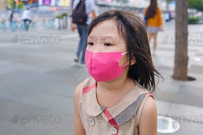 Asian child wearing mask in city street
