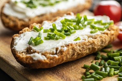 Crispbread with creamy cheese., green chive and tomatoes