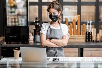 Saleswoman in medical mask in cafe or small shop
