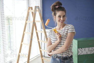 Portrait of ambitious woman with paint roller