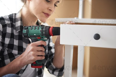 Independent woman repairing furnitures with electronic drill