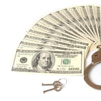 Close-up of metal handcuffs, keys and american dollars cash pack