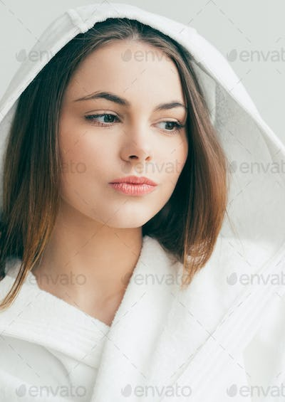 Beautiful young girl in a bathrobe, smiling and smears. Studio shot.