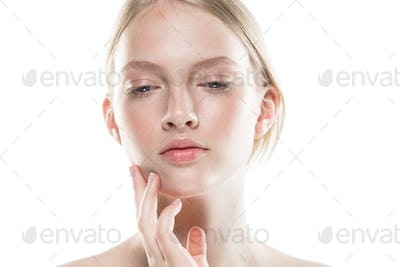 Young woman with beauty skin hand touching face isolated on white