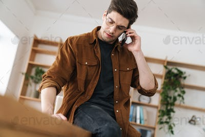 Image of serious young man talking cellphone while working