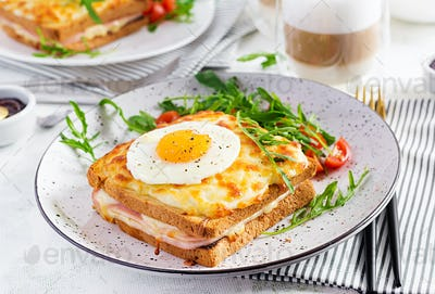 Croque madame sandwich and a cup of latte macchiato coffee on the table