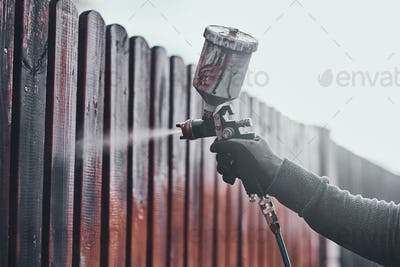 Diligent working is applying colour to the fence with airbrush