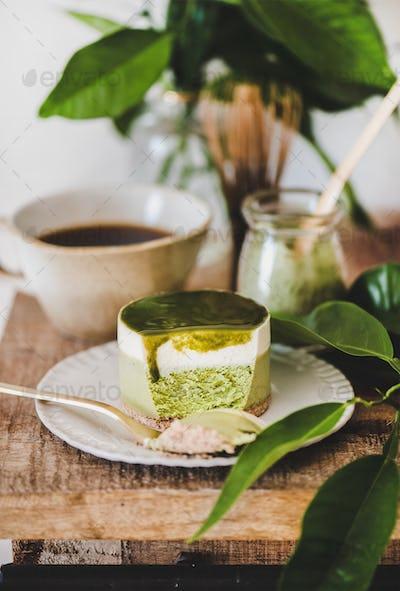 Green matcha cheesecake and coffee in mug on kitchen counter