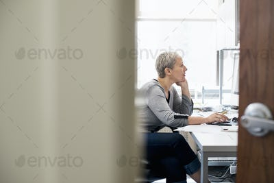 A woman working in an office alone. Focusing on a task, using a computer.