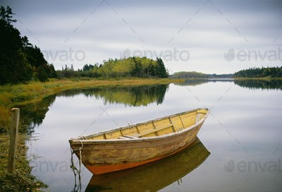 Small wooden dory or rowing boat moored on calm water, Savage harbor on Prince Edward Island Canada