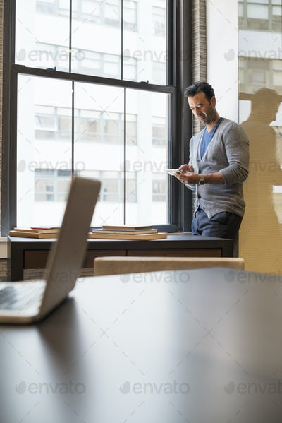 Office life. A man standing by a window in an office checking his smart phone.