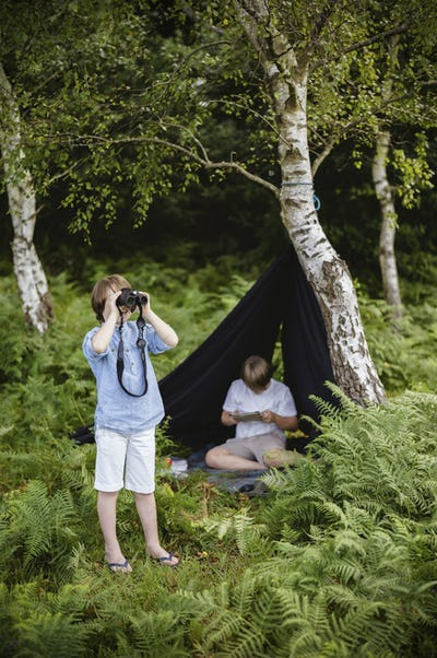 Two boys camping, one sitting under a black canvas shelter,  boy looking through binoculars,