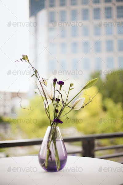 A table on a terrace in the city, vase of flowers, Small purple and white lily and orchid flowers