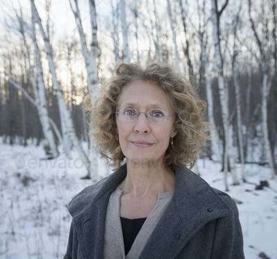 A mature woman with curly read hair, wearing a coat. Standing on a snowy path through woodland.