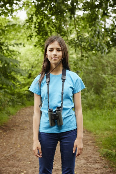 A young girl, a birdwatcher in a wood with binoculars around her neck.