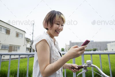 A woman pushing a bicycle while looking at her cell phone.