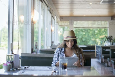 A young woman seated at a table in a diner, wearing a straw hat Using a digital tablet.