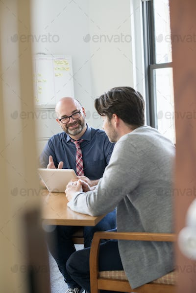 Two business colleagues in an office talking and referring to a digital tablet.