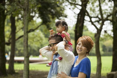 Family in a park. Two parents and a toddler.