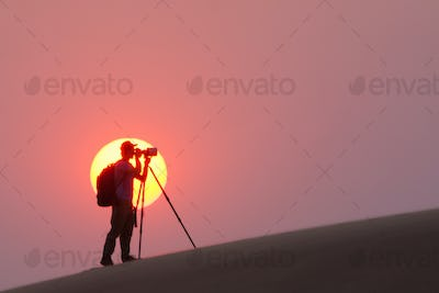 Photographer silhouetted in the setting sun in the Namib Desert, Namibia