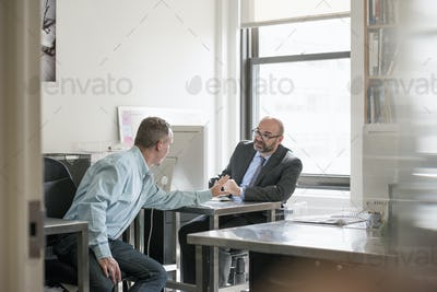Office life. Two men seated talking to each other.