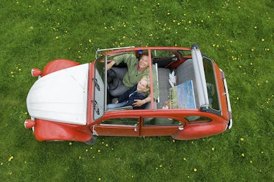 View from above of two people, a couple in a car with the roof open.