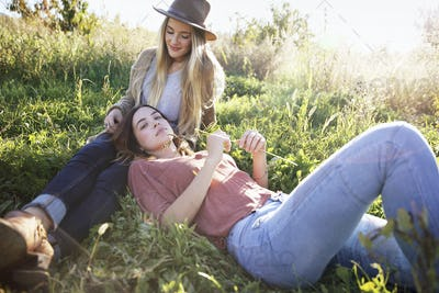 Apple orchard. Two women lying in the grass.