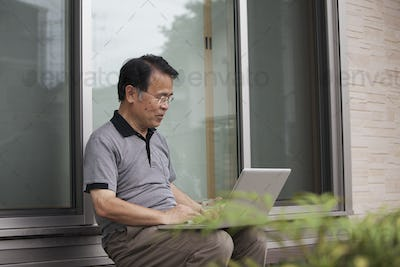A man sitting outside a house. Holding a laptop computer.