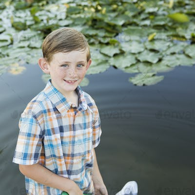 A young boy standing in shallow water with a fishing net.