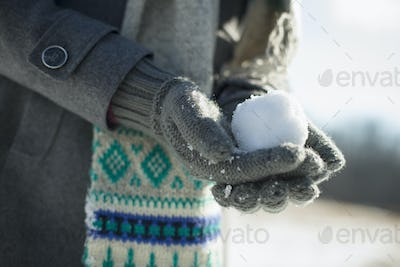 A young woman holding a small snowball in her gloved hands.
