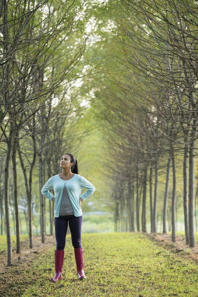 A woman between two rows of trees, looking upwards.