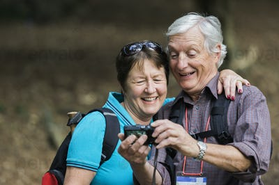 A mature couple looking at a digital camera, laughing.