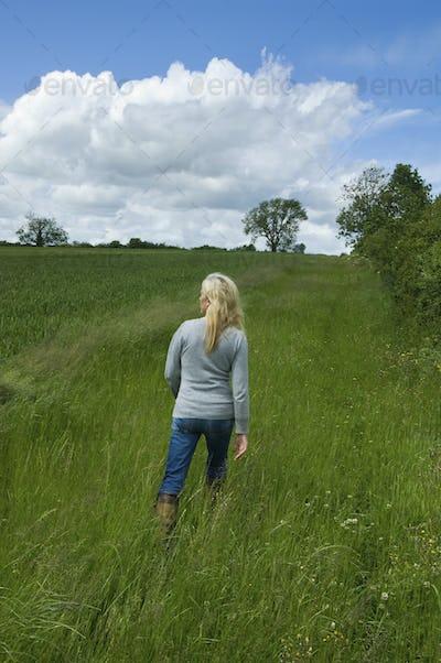 A woman walking in long grass in a meadow.