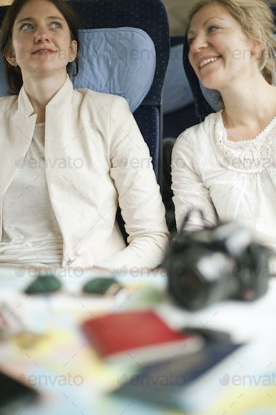 Two women on a train, side by side, Camera, passports and sunglasses on a table