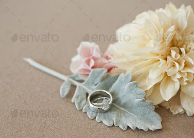 Three decorative accessories for a wedding. Flowers and a leaf shape. A finger ring.
