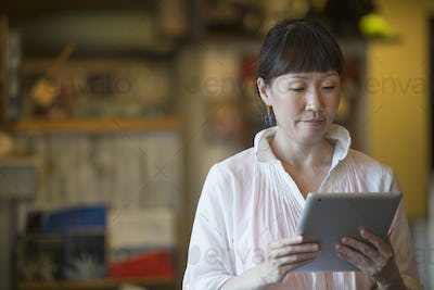 Woman standing in a cafe, holding a digital tablet.