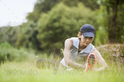 A woman preparing for exercising outdoors, stretching.