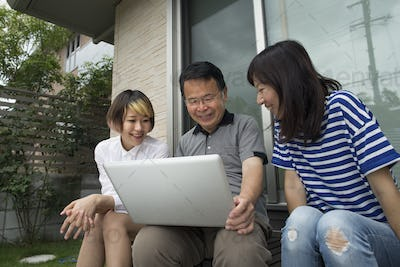 A man and two women sitting outside a house. Holding a laptop computer.
