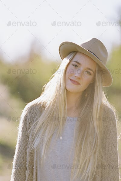 Apple orchard. Portrait of a woman with long blond hair, wearing a hat.