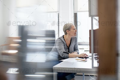 A woman working in an office at her desk, using a computer mouse.