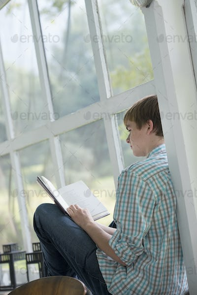 A young person sitting reading a book.