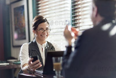 A man and woman working over lunch, seated at their desks and holding smart phones,