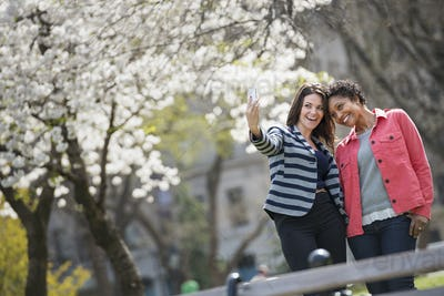 City in spring time, young woman holding out a phone to take a selfie