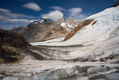 Several hikers on a glacier and Fitz Roy mountain in the background, Argentina