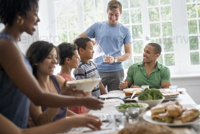 A family gathering, men, women and children around a dining table sharing a meal.