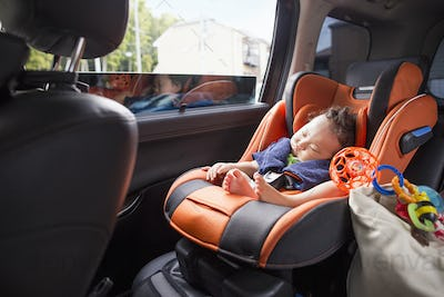 A mother and her young baby boy in a car.