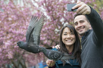 Man and woman in the park, taking a selfie, pigeon perched on the woman's wrist