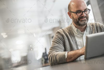 Office life. A man sitting at a table, working on a laptop.
