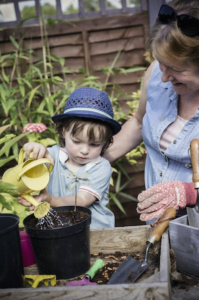 A woman and a young child water new seeds planted in a pot.