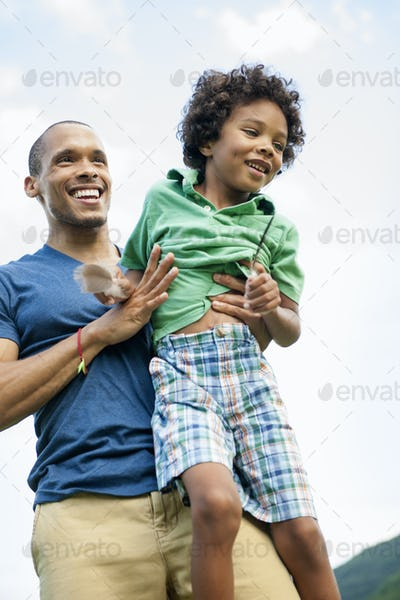 A man lifting his son up in his arms, playing outdoors.